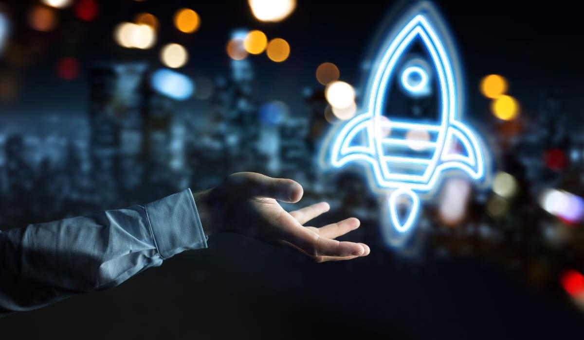 Foto hellbau leuchtende Rakete startet von Hand - Bildlich für Start-ups und Gründungsberatung