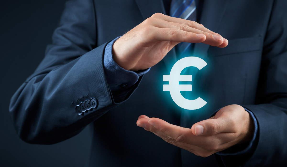 Hellblau leuchtendes Eurozeichen geschützt durch Hände - bildlich für Steuerberatung